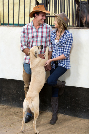 man dog: cheerful american western couple playing with their dog inside stables Stock Photo