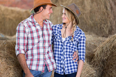cheerful couple looking at each other in barn photo