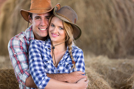 cowgirl and cowboy: portrait of young cute farming couple hugging in barn Stock Photo