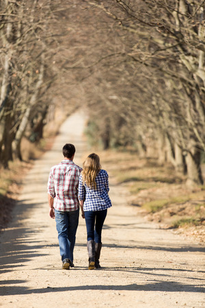 back view of lovely young couple walking on country road in fall