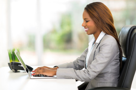 attractive african office worker using laptop computer