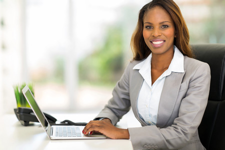 african women: happy young african american businesswoman using computer in office