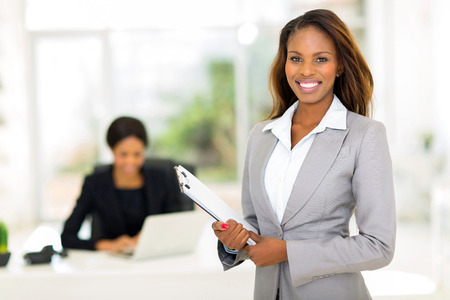 mujer trabajadora: hermosa empresaria africana la celebraci�n de portapapeles Foto de archivo