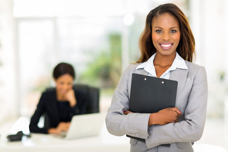 african american woman business: black business woman holding clipboard with colleague on background