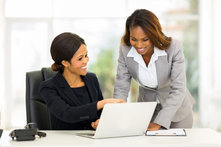 charming business lady: two african business women working at the office on a computer