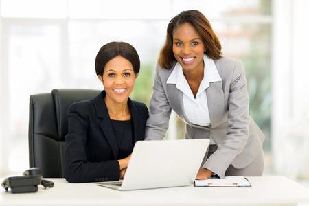 mujeres trabajando: retrato de la hermosa mujer de negocios del afroamericano en el cargo Foto de archivo