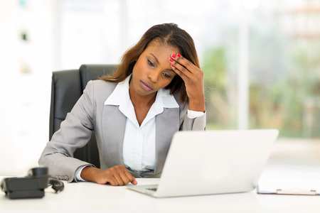 sad african american businesswoman sitting in modern office photo