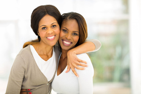 african american mother and daughter: cheerful african mother and daughter hugging at home