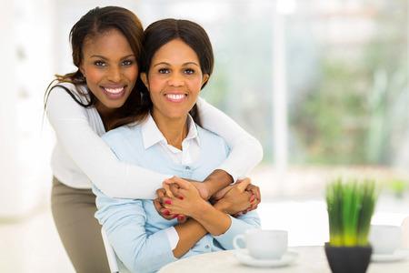 black girl: liebevolle afrikanische Tochter umarmt im mittleren Alter Mutter zu Hause