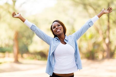 屋外に広げられた腕によって幸せなアフリカの女性