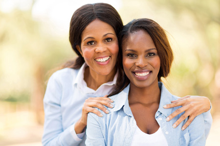 african ethnicity: portrait of happy middle aged african mother and adult daughter outdoors
