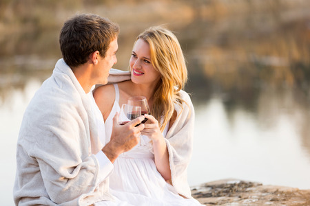 snuggle: cute young couple sitting by a lake with wine