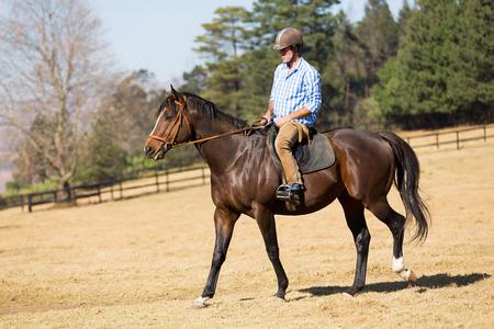 parapente: hombre joven que monta un caballo en el campo