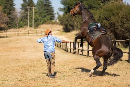 unease: cowboy taming a loosing racing horse Stock Photo