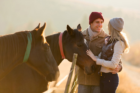 farm girl: lovely young couple petting a horse in a paddock