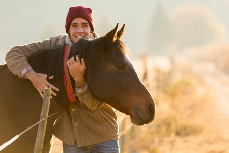 portrait of happy man hugging his horse in the ranch Foto de archivo