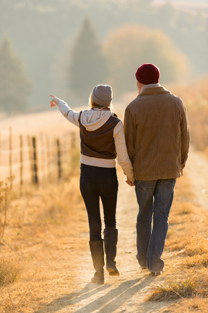 lifestyle outdoors: rear view of young couple walking in country road