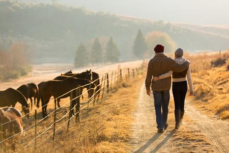 hombre con sombrero: Vista posterior de la joven pareja caminando de la carretera de la granja Foto de archivo