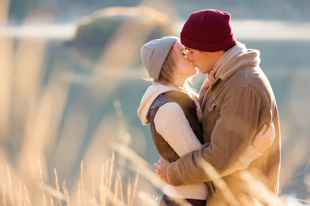 winter couple: loving young couple kissing by the lake in winter morning