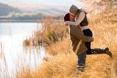 novios besandose: encantadora pareja joven besos al aire libre en oto�o