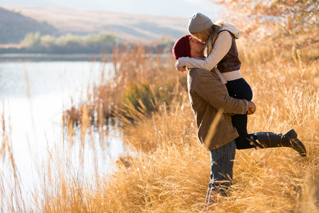 young couple hugging kissing: lovely young couple kissing outdoors in autumn
