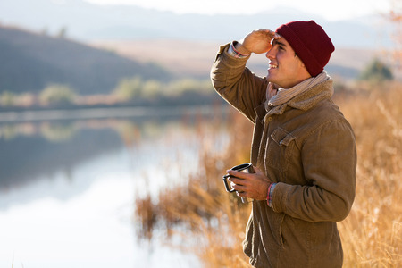 happy young man holding coffee mug and looking into distance in winter morning