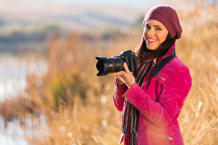 beautiful young woman holding a dslr camera outdoors in autumn Stock Photo