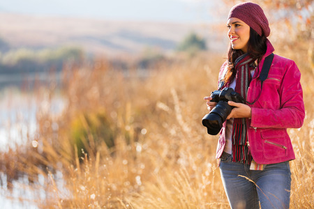 female photographer: young female photographer holding a camera outdoors in autumn