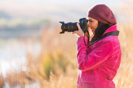happy female photographer taking photos outdoors in fall photo