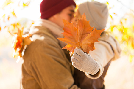 woman from behind: young couple kissing behind big leaves in autumn