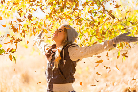 autumn leaves falling on happy young woman in forest