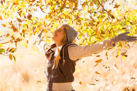 herfst bladeren vallen op de gelukkige jonge vrouw in het bos