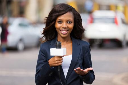 close up portrait of pretty african female news reporter in live broadcasting Foto de archivo