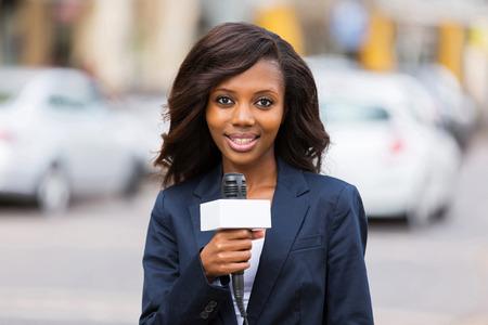 reportero: feliz periodista africano femenino que trabaja al aire libre