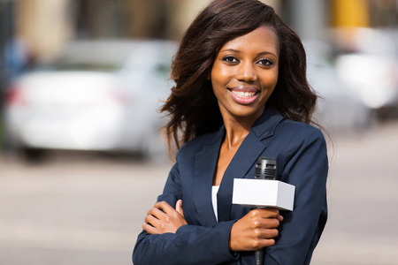american media: portrait of beautiful african news reporter standing outdoors
