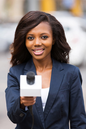 beautiful african news reporter interviewing with microphone photo