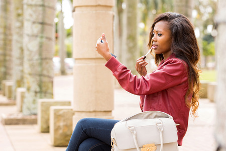 woman mirror: beautiful african woman holding mirror and applying lip gloss