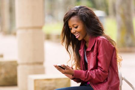 chaqueta: alegre mujer africana que usa el teléfono inteligente al aire libre