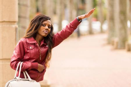 hailing: pretty african woman hailing a taxi cab Stock Photo