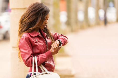 watch city: young african woman looking at her watch in urban street