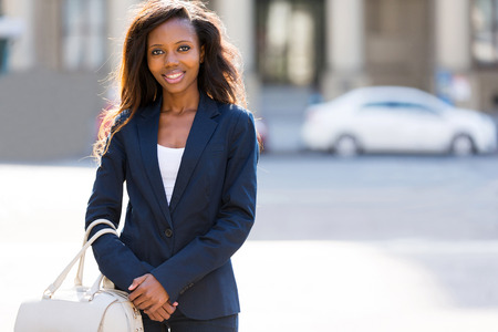 happy african woman: pretty african woman standing in the urban street