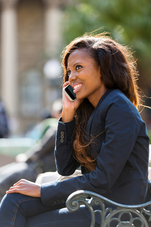 black lady talking: beautiful african woman sitting outdoors and talking on cell phone