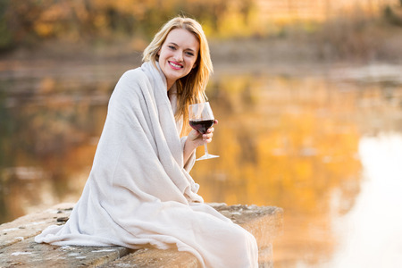 smiling young woman sitting on pier and drinking red wine at sunset photo