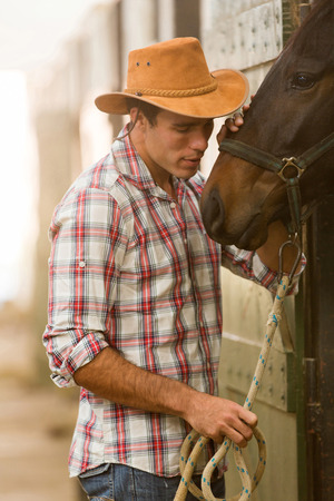 breeder: young cowboy whispering to a horse in stable Stock Photo