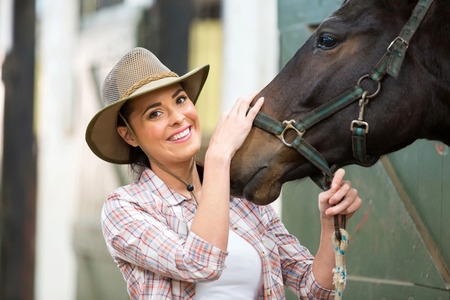cowgirls: happy cowgirl and her horse in stable Stock Photo