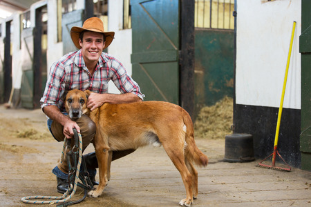 working cowboy: handsome cowboy and his dog inside stables  Stock Photo
