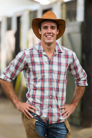 portrait of american cowboy standing in stables