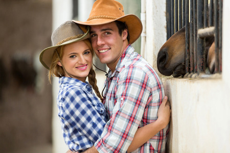 modern love: cute young western couple hugging in stable Stock Photo