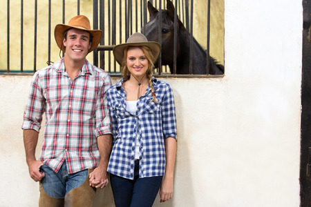 happy cowboy and cowgirl couple holding hands inside stables photo