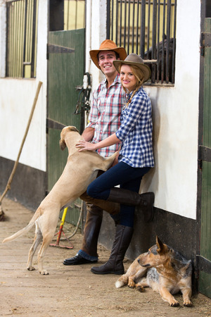 young horse farming couple and their dogs in stables photo